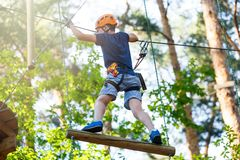 Cute young boy in helmet with climbing equipment in the rope amusement park. Summer camp, holidays. Concept royalty free stock photo