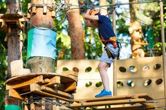 Cute young boy in helmet with climbing equipment in the rope amusement park. Summer camp, holidays. Concept royalty free stock photography