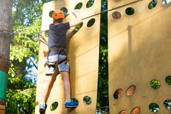 Cute young boy in helmet with climbing equipment in the rope amusement park. Summer camp, holidays. Concept royalty free stock photos