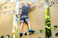 Cute young boy in helmet with climbing equipment in the rope amusement park. Summer camp, holidays. Concept stock images
