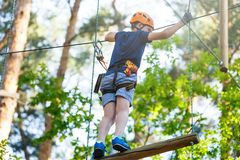 Cute young boy in helmet with climbing equipment in the rope amusement park. Summer camp, holidays. Concept royalty free stock image
