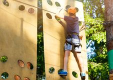 Cute young boy in helmet with climbing equipment in the rope amusement park. Summer camp, holidays. Concept stock photo