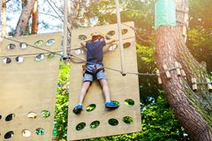 Cute young boy in helmet with climbing equipment in the rope amusement park. Summer camp, holidays. Concept stock photography