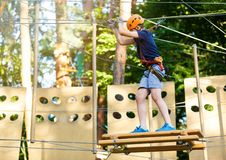 Cute young boy in helmet with climbing equipment in the rope amusement park. Summer camp, holidays. Concept stock photos