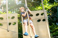 Cute young boy in helmet with climbing equipment in the rope amusement park. Summer camp, holidays. Concept royalty free stock images