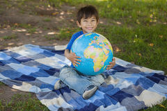 Cute young boy holding globe at park. Full length portrait of a cute young boy holding globe at the park Royalty Free Stock Photo