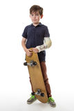 Cute young boy holding a skateboard Stock Images
