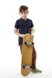 Cute young boy holding a skateboard. Full length portrait of a cute young boy holding a skateboard with a broken arm  isolated on white background Royalty Free Stock Images