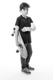Cute young boy holding a skateboard. Full length portrait of a cute young boy holding a skateboard with a broken arm  isolated on white background Stock Photos