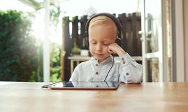 Cute young boy immersed in his music. Sitting listening on stereo headphones attached to a tablet with his head resting on his hand and a smile of bliss Royalty Free Stock Image