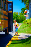 Cute young boy, kid getting on the school bus, ready to go to school Stock Photo