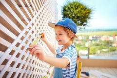 Cute young boy, kid helps father with renovation of wodden pergola wall on rooftop patio zone. Cute young boy, kid helps father with renovation of wodden pergola Stock Photography