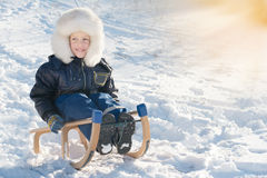 Cute young boy laughing as he is sledging downhill Stock Photos