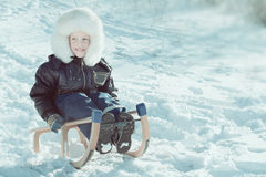 Cute young boy laughing as he is sledging downhill Stock Photo