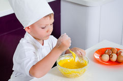 Cute young boy learning to bale a cake Royalty Free Stock Images