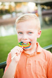 Cute young boy licking a large colorful lollipop outdoors Royalty Free Stock Images