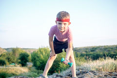 Cute Young Boy Lifting Dumbbell on Top of Boulder Royalty Free Stock Images