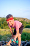 Cute Young Boy Lifting Dumbbell on Top of Boulder Stock Image