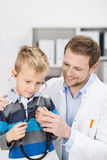 Cute young boy listening to his heartbeat Stock Photos
