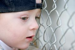 Cute young boy looking through fence. Cute young boy wearing a baseball cap and looking through a chain link fence Stock Image
