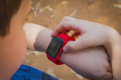 Cute young boy looking at his red smart watch and touching it Royalty Free Stock Photography