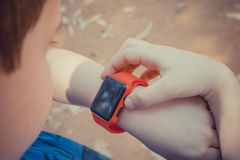 Cute young boy looking at his red smart watch and touching it Stock Photography