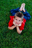 Cute young boy lying in the grass Royalty Free Stock Photos