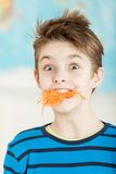 Cute young boy with a mouth stuffed with carrot Royalty Free Stock Image