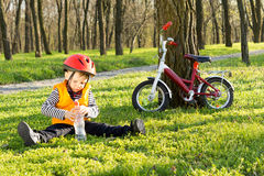 Cute young boy out riding on his bicycle. Stopping for a drink of bottled water sitting on lush green grass in a wooded park with his bike leaning up against a Royalty Free Stock Photos