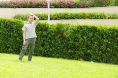 Cute young boy in the park is having fun green grass - summer time Royalty Free Stock Photo