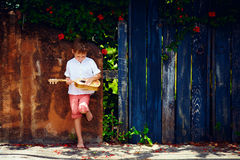 Cute young boy playing guitar near the summer old fence Stock Photo