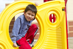 Cute young boy playing on playground equipment Royalty Free Stock Photo