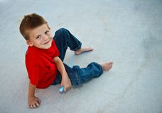 Cute young boy playing with sidewalk chalk Royalty Free Stock Image