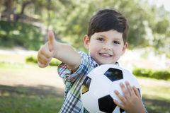 Cute Young Boy Playing with Soccer Ball in Park Royalty Free Stock Photography