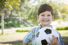 Cute Young Boy Playing with Soccer Ball in Park Stock Images
