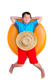 Cute young boy relaxing on an inner tube. Cute barefoot young boy relaxing on a colorful bright orange inner tube or floaty with a straw sunhat on his stomach Stock Images
