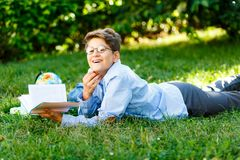Cute, young boy in round glasses and blue shirt reads book while lying on the grass in the park. Education, back to school stock photography