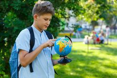 Cute, young boy in round glasses and headphones in blue shirt with backpack holds globe and point on it. Education, back to school. Concept royalty free stock image