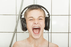 Cute young boy singing under a shower Royalty Free Stock Photo