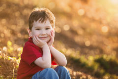 Cute Young Boy Sitting on a Hillside. A cute young boy smiles at the camera, holding his head in his hands, with a sparkling bokeh background Royalty Free Stock Photos