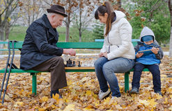 Cute young boy sitting on a park bench holding a tablet computer while his mother and grandfather play chess. Alongside him stock photography