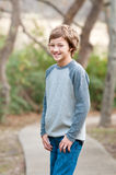 Cute young boy standing on sidewalk looking at camera Royalty Free Stock Images
