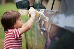Cute young boy washing car with sponge in a garden Royalty Free Stock Photos