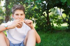Cute, young boy in white t shirt sits on the grass and takes a slice of pizza in the summer park. Boy eats pizza royalty free stock photo