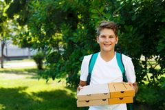 Cute, young boy in white t shirt stands on the grass and holds boxes with pizza in the summer park. Boy eats pizza stock images
