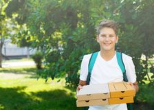 Cute, young boy in white t shirt stands on the grass and holds boxes with pizza in the summer park. Boy eats pizza royalty free stock photos