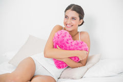 Cute young brown haired model in white pajamas hugging a heart-shaped pillow Royalty Free Stock Images