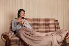 Cute young brunette covered in a blanket on a cold day Royalty Free Stock Photos