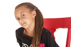 Cute young brunette girl glancing sideways sitting Stock Photos