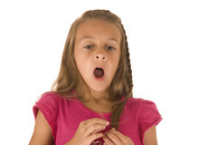 Cute young brunette girl in pink shirt yawning Royalty Free Stock Photos